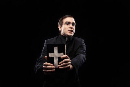 Photo pour Portrait of frightened young catholic priest against black background - image libre de droit