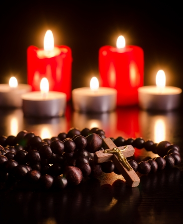 Closeup of wooden rosary on candlelight background