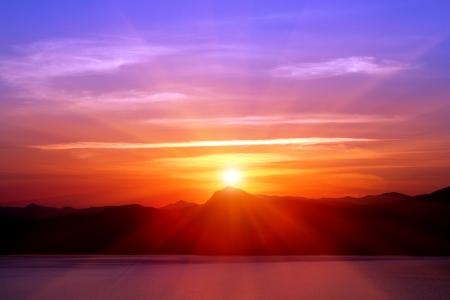 sunset over mountains near sea