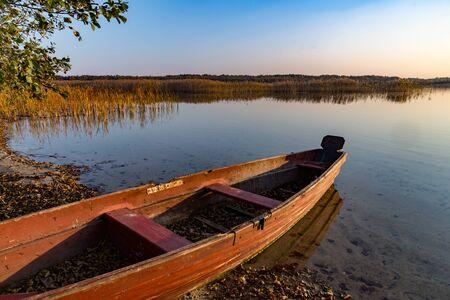 Photo pour old wooden boat on lake. evening landscape, autumn - image libre de droit