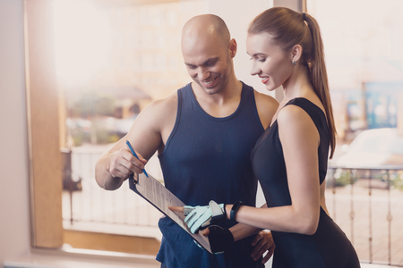 Photo for Trainer writes a fitness program training the girl. The program of physical training for effective results when working in the gym. Work on physical labor with an individual trainer in a fitness club. - Royalty Free Image