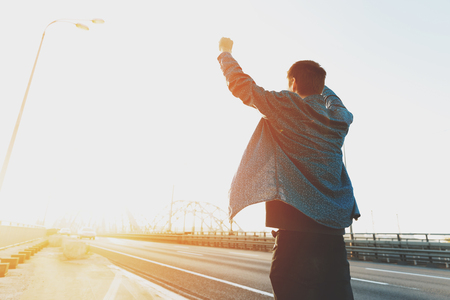 Photo for Happy man is standing with his arms raised up. Happy man jumping for joy with his hands up. Happy young man at sunrise on a busy bridge cars. The concept of a free and joyful person - Royalty Free Image
