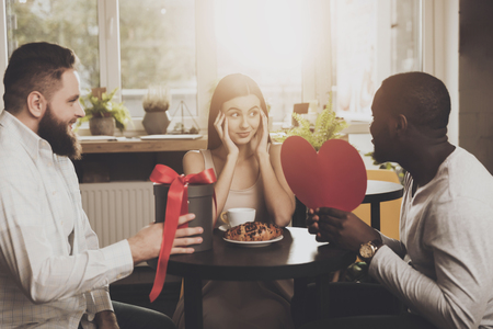 Photo pour Two men congratulate young beautiful woman. Two young men prepared a surprise for a beautiful girl on Valentines Day in the form of gifts. Festive mood and pleasant impressions. - image libre de droit