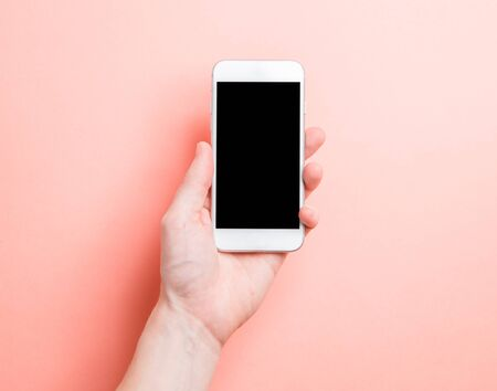 Photo for Minimalistic layout of the photographer. Hand with telephone on a pink background.  - Royalty Free Image