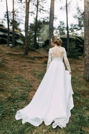 Photo for Elegant ceremony in European style. Beautiful bride in white flying dress in the forest.  - Royalty Free Image
