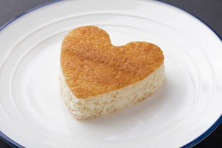 Photo pour A heart-shaped cupcake on a white plate with a blue border. Lovers day and birthday celebration concept - image libre de droit
