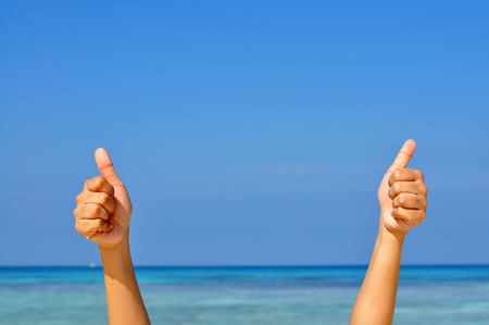 Photo pour Two hands making the sign of Like with the blue sea and sky background - image libre de droit