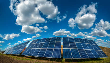 Photo pour Solar energy station panel system on plowed field and sky with beautiful clouds - image libre de droit