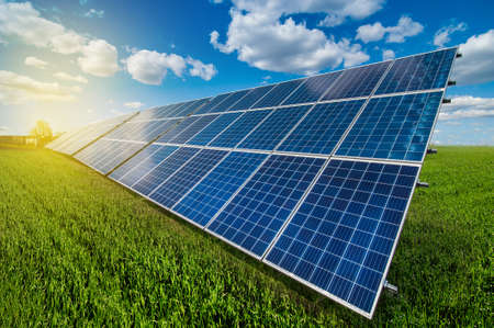 Photo pour Solar energy panel system power at green grass and sky with clouds and sunshine - image libre de droit