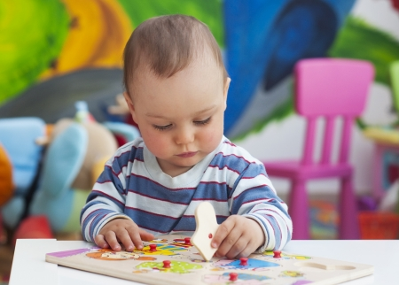 Small toddler or a baby child playing with puzzle shapes on a low table in a colorful children room in a nursery or preschool