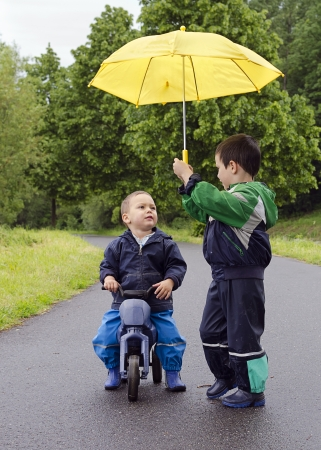 Children friends with yellow umbrella and toy bike in the rain. の写真素材