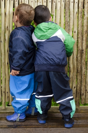 Two children, boys, looking through the wooden fence or wall, back view. の写真素材