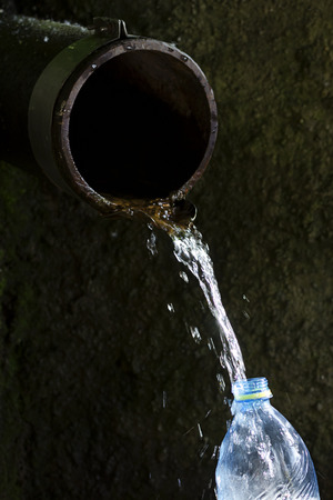 Old rustic water pipe with running drinking water and plastic bottle being filled up, aid concept.