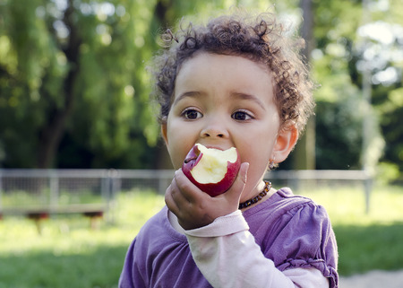 Foto de Child girl eating an apple in a park in nature. - Imagen libre de derechos