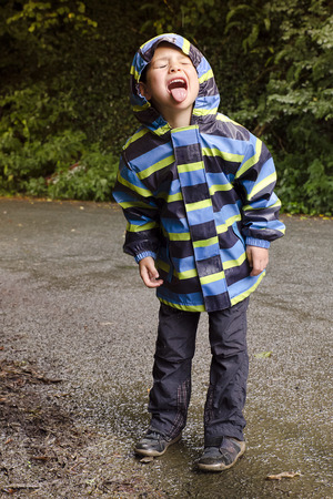 Child boy catching dops of rain water in his open mouth at rainy day at nature.の写真素材