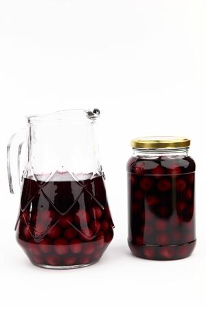 Compote with cherries in jar and ewer