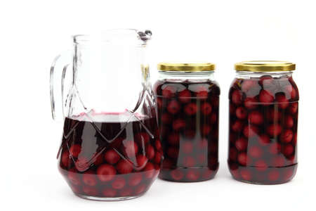 Compote with cherries in jars and ewer