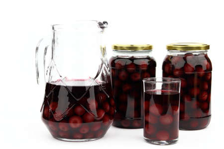 Compote with cherries in jars, glass and ewer