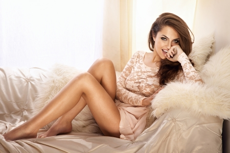 Fashion photo of beautiful young woman wearing lace dress, relaxing and smiling in bright room, on the white couch