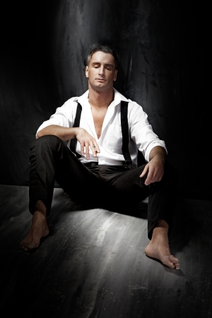 Portrait of a handsome young man wearing white shirt and smoking while sitting on the floor