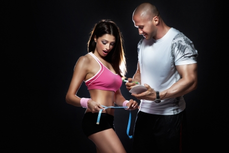 Photo of attractive couple at the gym. Coach measured body of beautiful brunette woman with perfect fitness shape.