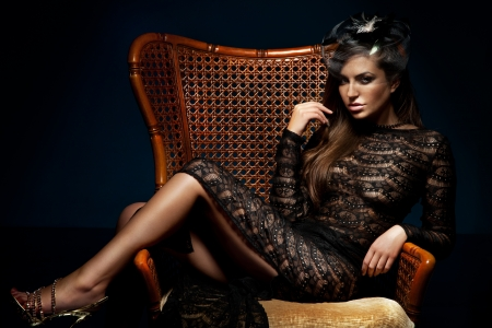 Photo of beautiful sexy brunette woman posing, sitting on chair, wearing black elegant dress. Looking at camera.の写真素材