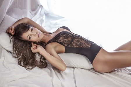 Foto de Sensual brunette woman with long curly hair lying in white bed, posing in sexy black lingerie, looking at camera. - Imagen libre de derechos