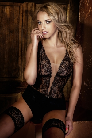 Beautiful blonde woman sitting wearing sexy lingerie, looking at camera.の写真素材