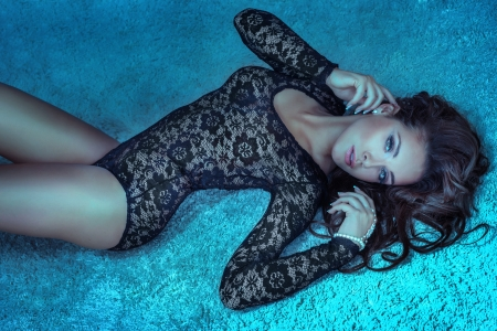 Sensual brunette woman with long hair lying on carpet in underwear, looking at camera.