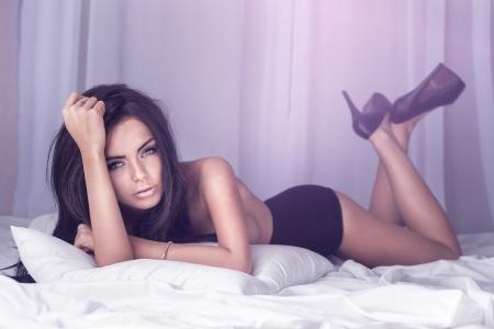 Sensual brunette woman posing in big white bed. Studio shot.