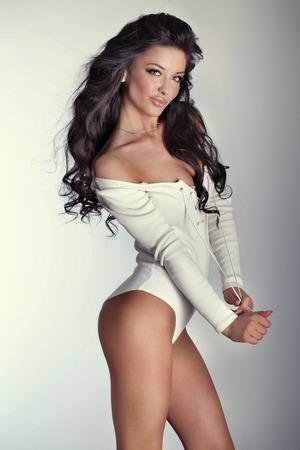 Foto de Romantic brunette woman posing in studio, looking at camera and smiling. - Imagen libre de derechos
