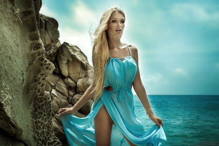 Beautiful blonde woman walking on the beach, wearing fashionable blue dress. Sexy look. Summer photo.