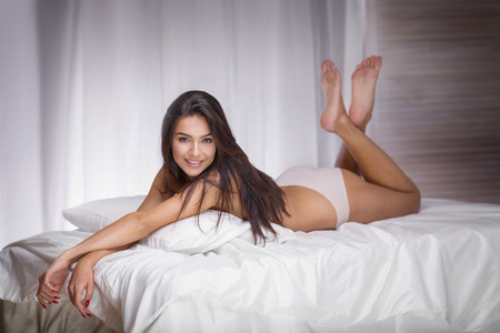 Photo for Sensual brunette woman with long slim legs lying in bed, looking at camera. - Royalty Free Image