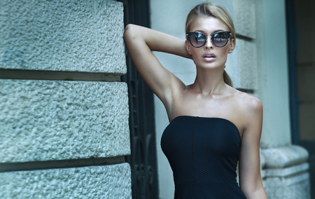 Fashionable blonde woman posing outdoor, wearing elegant mini dress and sunglasses.
