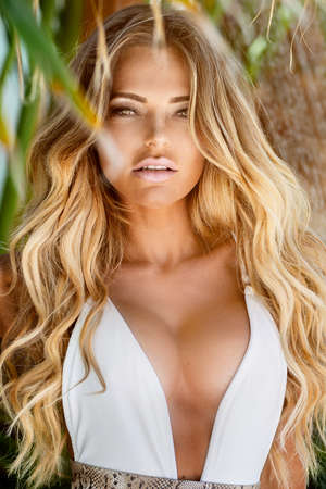 Photo pour Beautiful sexy blonde woman in white swimsuit with tanned body sensual posing between palm trees. - image libre de droit