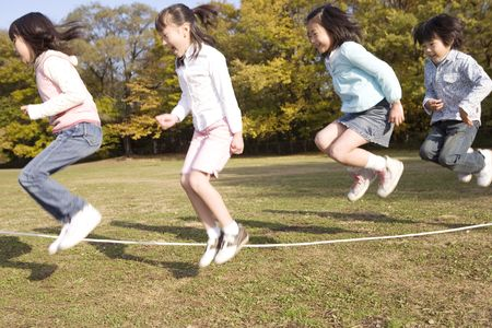 Japanese children skip a rope in the park