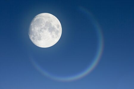 Moon and circled rainbow in the blue sky