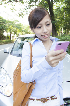 OL to operate the smart phone in front of a carの写真素材