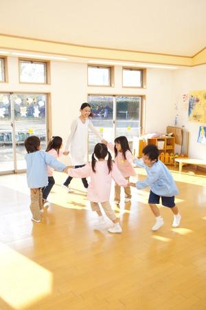 Kindergarten teachers and kindergarten children dancing in a circle
