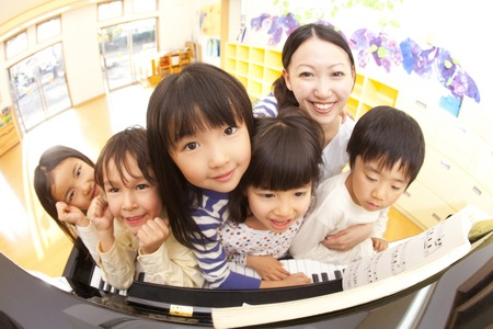Nursery school children and nursery teacher smiling in front of the piano