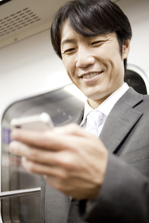 Businessman smiling with a smartphone