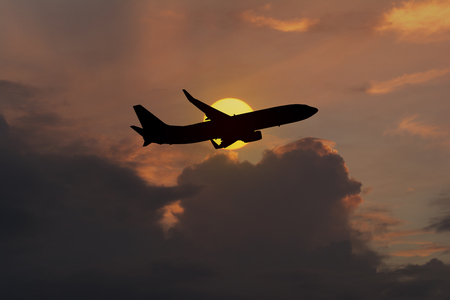 Silhouette of an airplane taking off on sunset background