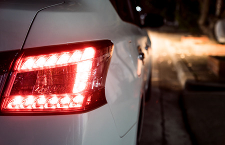 Photo pour Rear light of white car at night. Break light and head light are active. - image libre de droit