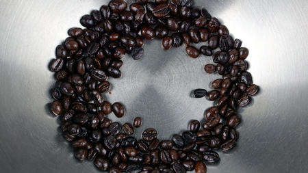 Dark roasting coffee beans in stainless pot.