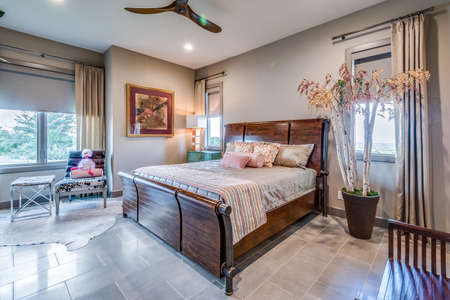 Photo pour Wood bed frame and bed in staged bedroom - image libre de droit