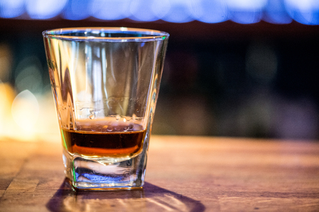 Glass of scotch whiskey on wooden background with copyspace