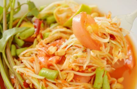 Somtum Thai green papaya salad tasted spicy sour and sweet on fork