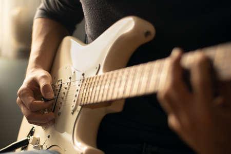 Photo pour Man playing a white electric guitar. Close-up - image libre de droit