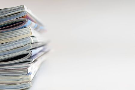 forefront of some magazines piled out of focus white background