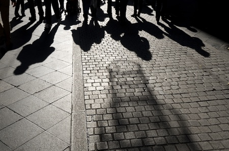 shadows of people walking along a  cobblestone street, Seville,  Andalucia, Spain